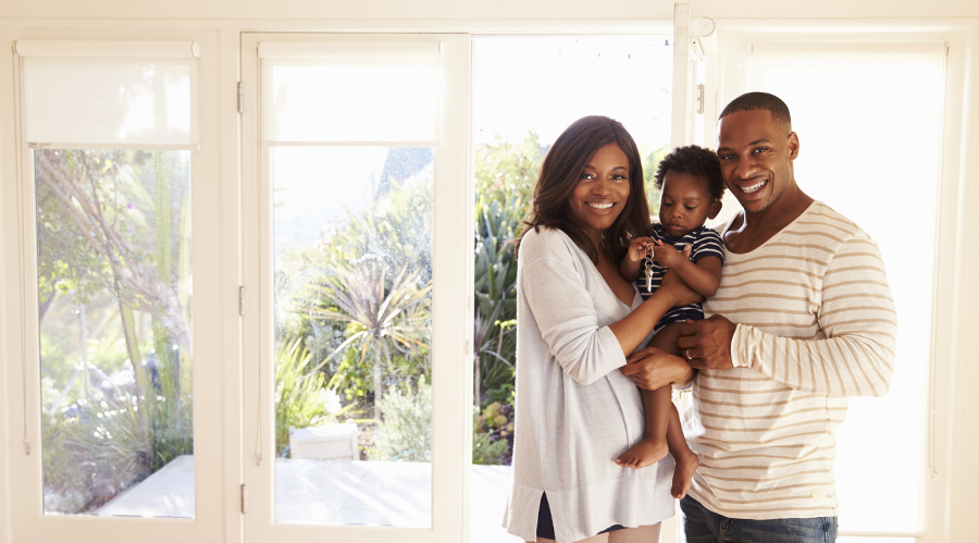 A young mother and father hold their toddler son while admiring their newly purchased house.