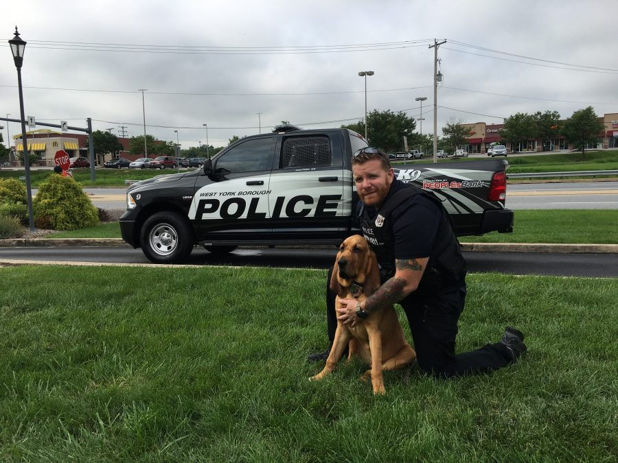 West York Borough policeman with K9 Detective Prince in front of a black police truck