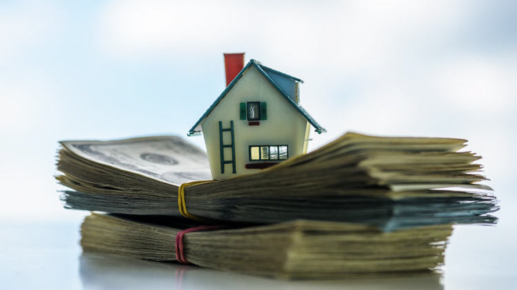 house figurine on top of stacks on money