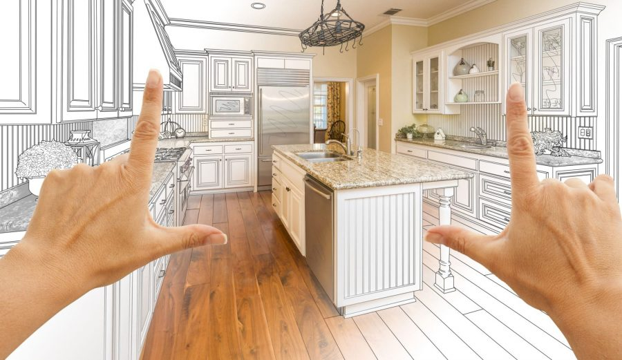 hands making a frame around a blueprint of a new kitchen