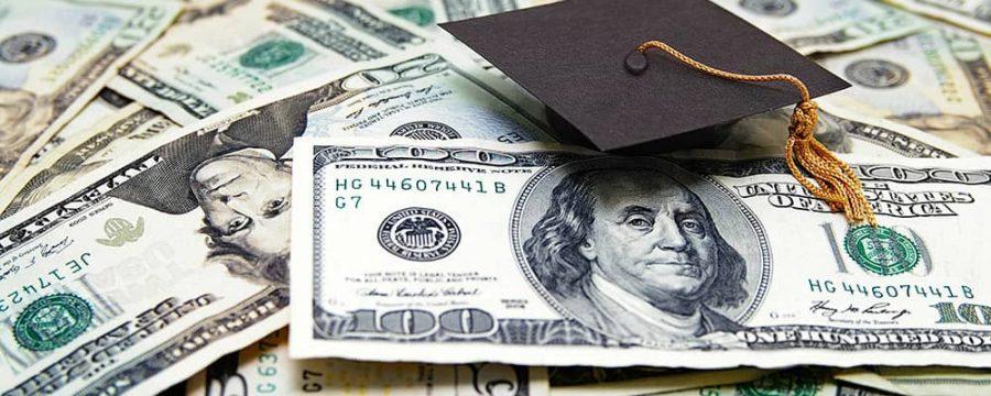 photo of graduation cap onto of dollar bills