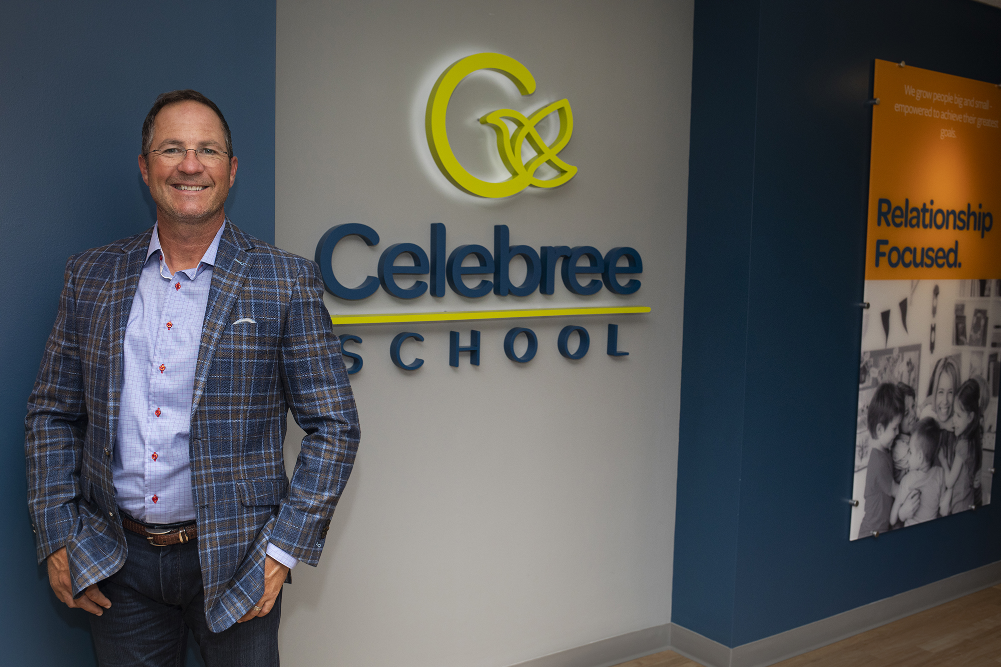 Richard Huffman, CEO of Celebree Schools, stands in front of wall with Celebree School logo
