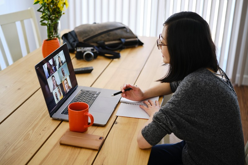 woman working from home and using laptop to have a virtual conference