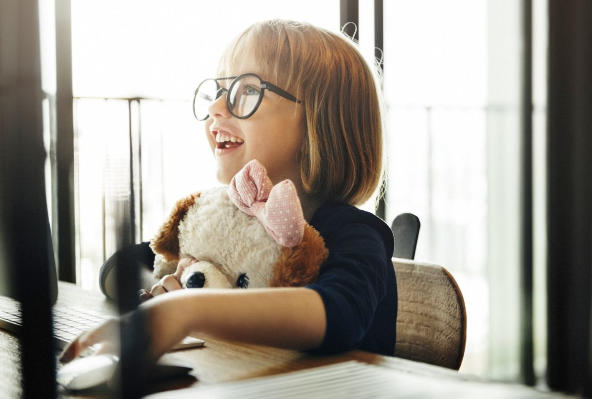 little girl sitting in front of computer holding stuffed dog