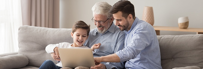 three generations sitting on couch looking at laptop