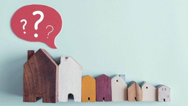 row of wooden homes with question marks