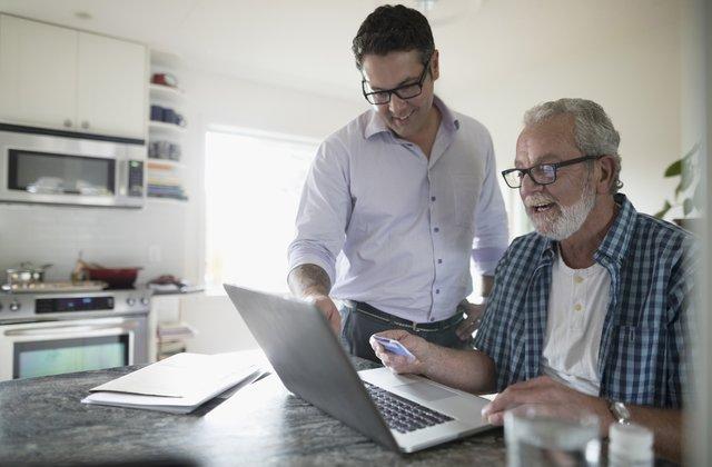 man helping elderly man with computer