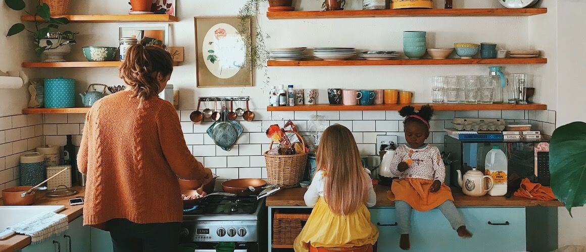 woman in kitchen with two girls