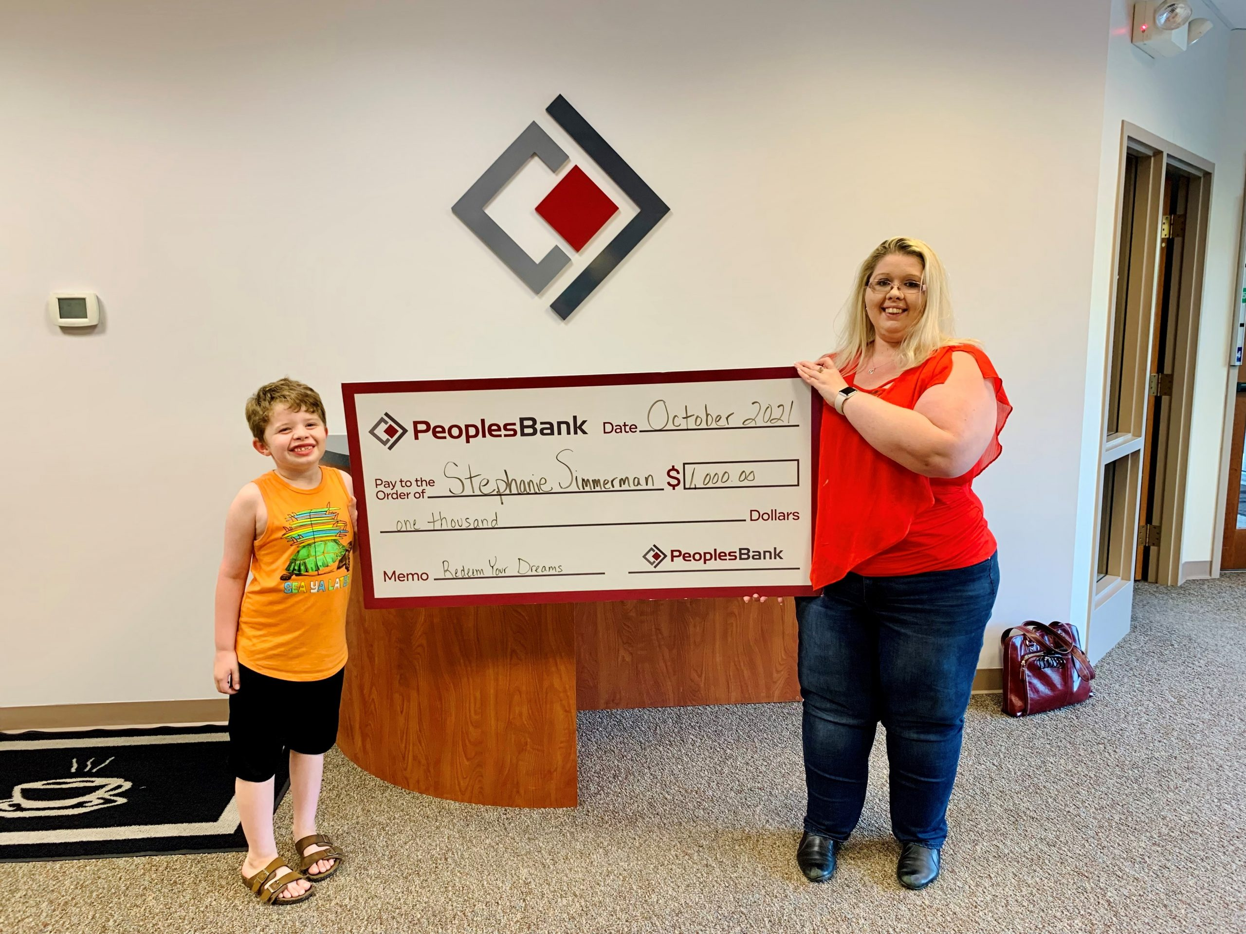 Stephanie Simmerman and son holding large check