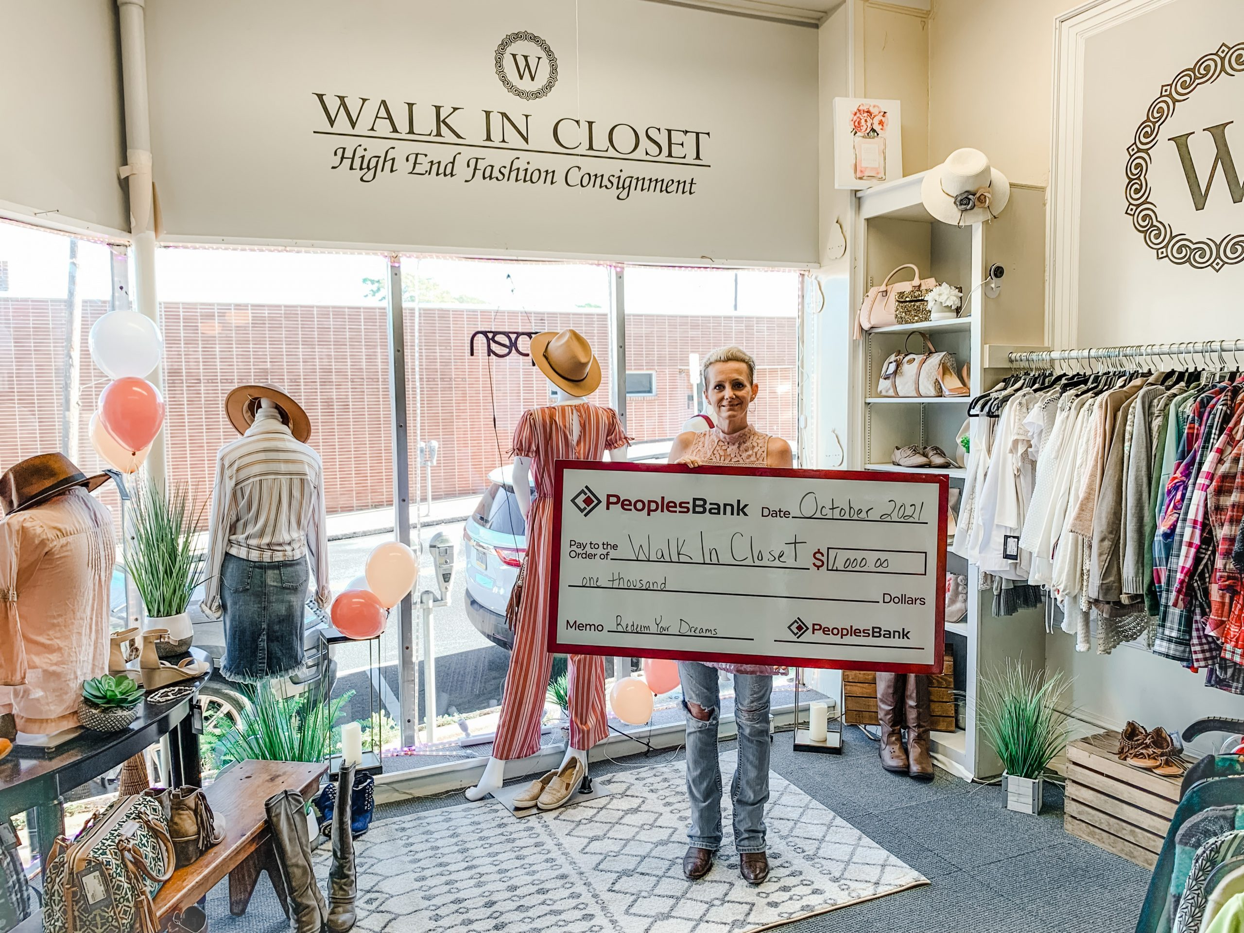 Laurie Miller holding large check in her store, Walk in Closet